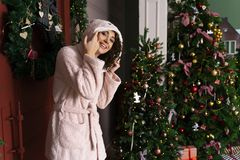 A beautiful smiling girl in a warm fluffy robe, dressed in a hood on her head, stands near the red door, decorated with fir royalty free stock images