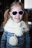 Beautiful smiling girl in warm knit scarf and sunglases in house Stock Images