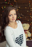 Beautiful smiling girl in warm white jacket sits near the window next to the wall in the lights Stock Photo