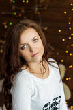 Beautiful smiling girl in warm white jacket sits near the window next to the wall in the lights Royalty Free Stock Photo