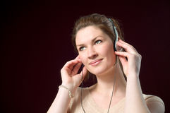 Beautiful Smiling Girl Wearing Music Headphones. Beautiful Smiling Redhead Girl Wearing Music Headphones isolated on dark background Stock Images