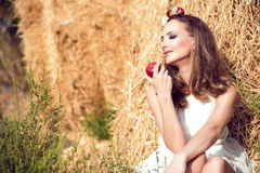 Beautiful smiling girl wearing white summer dress and floral head wreath sitting at the haystacks and holding a red apple Stock Photo