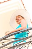 Beautiful smiling girl in white hat standing on the balcony Royalty Free Stock Photos