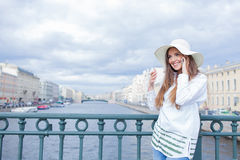 A beautiful and smiling girl in a white hat with wide brim is standing on the bridge and talking on the phone against the backgrou. Nd of blue clouds royalty free stock image