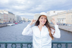 A beautiful and smiling girl in a white hat with wide brim is standing on the bridge and talking on the phone against the backgrou. Nd of blue storm clouds stock photography