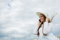 A beautiful and smiling girl in a white hat with wide brim is standing on the bridge and talking on the phone against the backgrou. Nd of blue clouds royalty free stock photos