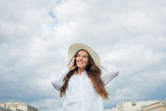 A beautiful and smiling girl in a white hat with wide brim is standing on the bridge and talking on the phone against the backgrou. Nd of blue storm clouds royalty free stock image