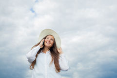 Beautiful smiling girl in a white hat with a wide brim talking on the phone on background of storm clouds.  stock photography