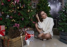 Beautiful smiling girl in a white sweater sits in the floor amon royalty free stock images
