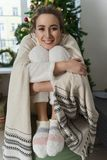 Beautiful smiling girl in a white sweater and warm socks sits wr royalty free stock photos