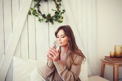Beautiful smiling girl 20-24 year old drinking water. On bedroom. Wearing knitted sweater stock photography