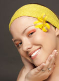 Beautiful smiling girl with a yellow flower Stock Photos