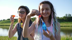 Beautiful smiling girls adolescent blowing soap bubbles at nature on sunny summer day. Beautiful smiling girlfriends adolescent blowing soap bubbles at nature on stock video footage