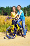 Beautiful smiling girls ride bicycle Royalty Free Stock Images
