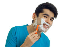 Beautiful smiling guy with foam on his face looks into the camera and shaves his beard machine Stock Images