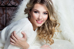 Beautiful smiling happy girl with bright makeup lies on the bed with fur in white sweater Royalty Free Stock Photography