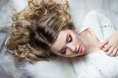 Beautiful smiling happy girl with bright makeup lies on the bed with fur in white sweater Royalty Free Stock Photos