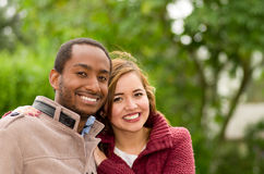 Beautiful and smiling happy interracial young couple in park in outdoors Royalty Free Stock Image