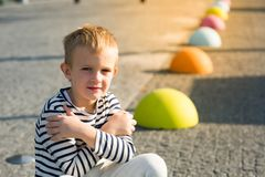Beautiful smiling happy little boy sitting on colored stones, looking at camera Stock Image