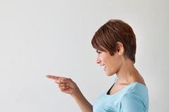 Beautiful smiling happy positive woman pointing to blank space Stock Photography