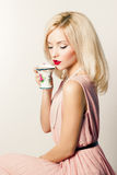 Beautiful smiling happy elegant girl with red lipstick in a pink dress in retro style drinks tea coffee from a small mugs Royalty Free Stock Photo