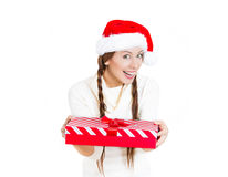 Beautiful smiling happy young woman wearing red santa claus hat giving present wrapped in ribbon to you Royalty Free Stock Image