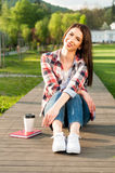 Beautiful smiling hipster relaxing in nature with coffee and boo Stock Photos