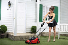 Beautiful smiling housemaid mows lawn by mower stock photos