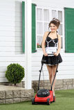 Beautiful smiling housemaid stands with lawn mower Royalty Free Stock Photo