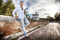 Beautiful smiling Italian man outdoors in Rome Italy. Tiber river from the bridge. A beautiful young Italian man posing outdoors on Milvian Bridge in the stock image