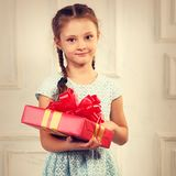 Beautiful smiling kid girl holding present box with red ribbon b Stock Image