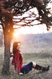 Beautiful smiling lady sitting under a tree with sunset on background royalty free stock photography
