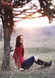 Beautiful smiling lady sitting under a tree with sunset on background. Beautiful smiling lady sitting under a tree with sunseton background Royalty Free Stock Photo