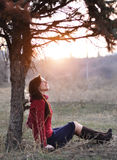 Beautiful smiling lady sitting under a tree with sunset on background Stock Photos
