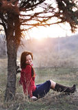 Beautiful smiling lady sitting under a tree with sunset on background royalty free stock photos