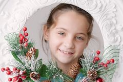 Beautiful smiling little girl on the background of Christmas dec. Orations from fir cones and branches Stock Image