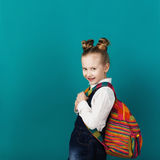 Beautiful smiling little girl with big backpack standing against. Blue wall. Looking at camera. School concept. Back to School Stock Photo