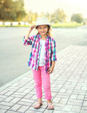Beautiful smiling little girl child wearing pink checkered shirt and hat. Beautiful smiling little girl child wearing a pink checkered shirt and hat in city Royalty Free Stock Photos