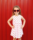 Beautiful smiling little girl child wearing a white dress and red sunglasses. Over colorful background Stock Images