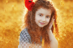 Beautiful smiling little girl with curly hair in the grass field Stock Image