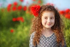 Beautiful smiling little girl with curly hair in poppies field a Royalty Free Stock Photos