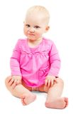 The beautiful smiling little girl in dress sits Stock Photo