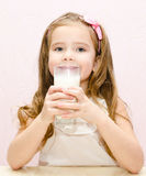Beautiful smiling little girl drinking milk Stock Images
