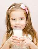Beautiful smiling little girl drinking milk. Isolated Royalty Free Stock Image