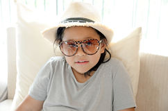 Beautiful smiling little girl in glasses sits at living room. (relax). Stock Photo