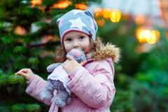 Beautiful smiling little girl holding christmas tree Royalty Free Stock Image