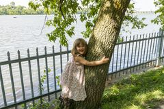 Beautiful smiling little girl hugging a tree trunk. With railing and river in the background, Ile-de-la-Visitation Nature Park, Montreal, Quebec, Canada Stock Photos