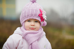 Beautiful smiling little girl in pink coat close up. Against color wall Royalty Free Stock Photography