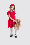 Beautiful smiling little girl in a red dress with a toy bear. Studio shot Stock Photos
