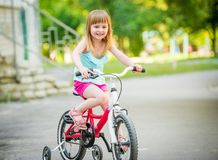 Beautiful smiling little girl riding bicycle. In a park Stock Photos